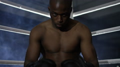 4K Aggressive fighter sits in corner of ring, psyching himself up for the fight. Stock Footage