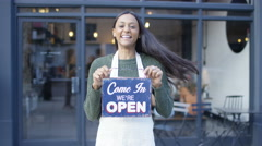 4K Excited female cafe owner holds up a sign to show she is open for business - stock footage