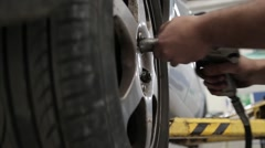 Attaching wheel to a car with pneumatic screwdriver Stock Footage