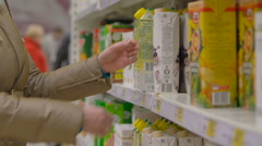 Young woman shopping for juice in supermarket Stock Footage
