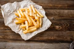 French fries on wooden table Stock Photos