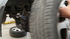 Attaching wheel to a lifted car - stock footage