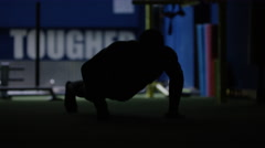 4K Unrecognizable MMA fighter in silhouette, training alone in dark gym Stock Footage