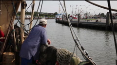 Fisherman at the railing and the boat leaves the harbor Stock Footage