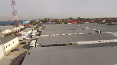 Low flying aerial perspective over industrial warehouses. Stock Footage