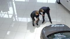 Salesman assisting customer in car showroom Stock Footage