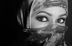 close-up beautiful mysterious eyes eastern woman wearing a hijab. black and - stock photo