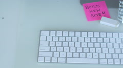 Build new website post it with keyboard and sketch pad close up - stock footage