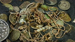 Treasure, gold jewelry and coins on a black sand. Close-up rotation. - stock footage