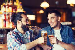 Stock Photo of happy male friends drinking beer at bar or pub