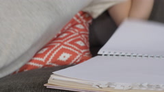 Artist begins drawing in sketchbook on couch Stock Footage