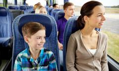 Stock Photo of happy family riding in travel bus