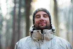 Man in nature wearing warm clothing looking happy and peaceful Stock Photos