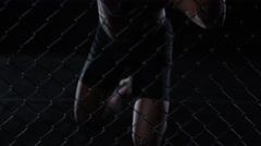 4K Muscular MMA fighter holding on to the fencing of the cage Stock Footage