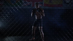 4K Muscular MMA fighter training alone in dark environment - stock footage
