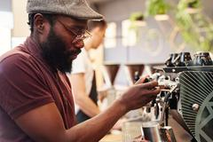Hipster Afro man working an espresso machine in coffee shop Stock Photos