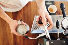 Barista using espresso machine to steam milk in metal jug Stock Photos