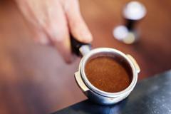 Hand holding portafilter for espresso machine containing ground Stock Photos