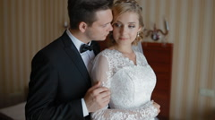 Bride and groom pose to photographer in a hotel room Stock Footage