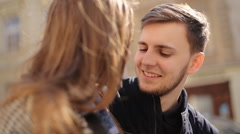 Young shy man talking to his girlfriend sitting on the bench at the street - stock footage