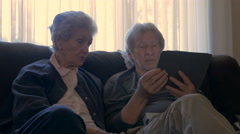 Two seniors sit next to each other and talk while holding a mobile tablet dolly Stock Footage