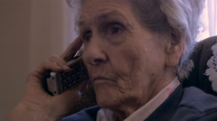 Hand held of an aging senior asking questions while on a landline telephone. Stock Footage