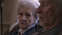 Two elderly older people talking while sitting next to each other on a sofa Stock Footage