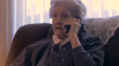 An aging senior in her 90s talks and laughs on a phone in her home in 4k dolly - stock footage