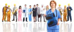 Smiling medical doctor over workers group. - stock photo