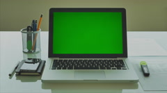 Stock Video Footage of Laptop with green screen ( Chroma key ) on modern glass table in the office 4K