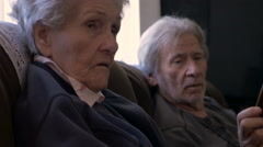 An elderly man shows a smart phone to an older woman in her 90s - stock footage