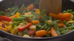 Frying vegetables in black pan Stock Footage