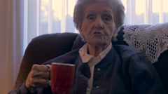 A senior women tells a story while drinking a cup of coffee - dolly shot in 4k Stock Footage