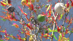 A festive Easter tree with colorful ribbons on it on a sunny and windy day Stock Footage
