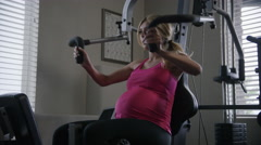 Low angle medium slow motion shot of pregnant woman lifting weights / Cedar Arkistovideo