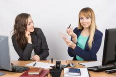 Two young pretty business woman sitting at a office table is divided into two - stock photo