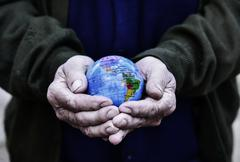 Old man with a world globe in his hands Stock Photos