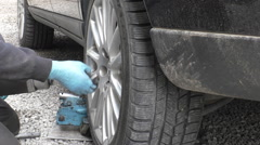 Removing car wheel on the roadside Stock Footage