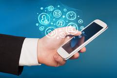 Hand holding smartphone with mobile app choices - stock photo