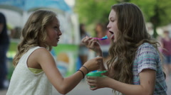 Medium shot of girls eating shaved-ice at funfair / Pleasant Grove, Utah, United Stock Footage