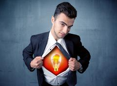 Businessman ripping off shirt and idea light bulb appears Stock Photos