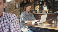 4K Young woman working on laptop in trendy city cafe - stock footage