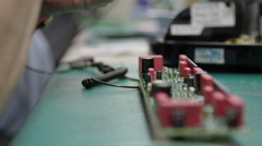 Close up of circuit boards being populated and created in factory setting - stock footage
