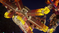 Low angle slow motion medium shot of spinning amusement park ride / Pleasant Stock Footage