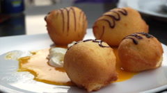 Eating fried banana and ice cream balls topping with chocolate dessert Stock Footage