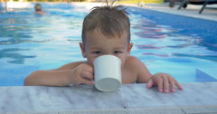 Little child drinking water in the swimming pool Stock Footage