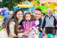 Father, mother, daughter enjoying fun fair ride, amusement park Kuvituskuvat