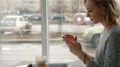 Young beauty woman writing message on cell phone in a street cafe. Looking down Stock Footage