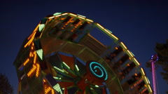 Low angle medium slow motion shot of glowing amusement park rides / Pleasant Stock Footage