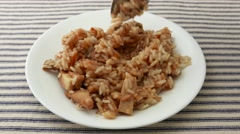 Stirring and eating a chicken with rice TV dinner Stock Footage